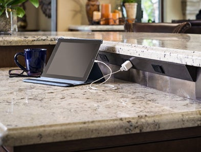 A tablet on a kitchen counter, plugged into a Task Lighting angle power strip.